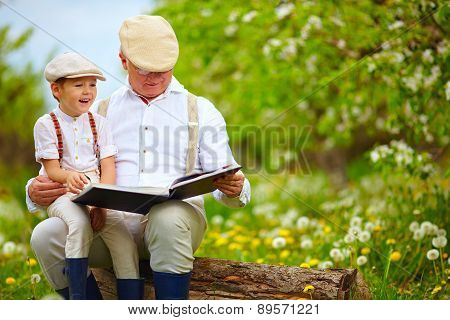 Grandfather Reading A Book To His Grandson, In Blooming Garden