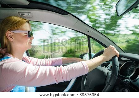 Smiling Beautiful Woman In Sunglasses Driving Car At High Speed