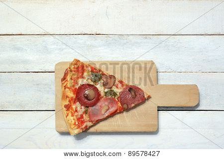 Slice of homemade pizza 4 seasons in a white wooden table of a rustic kitchen