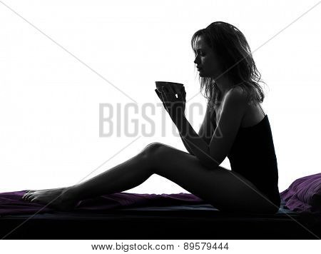 one woman drinking sitting on bed silhouette studio on white background