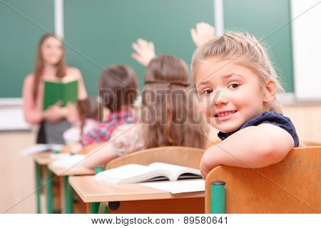 Pupil raising hand turned away from teacher