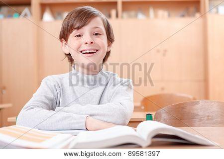Smiling boy sitting at desk