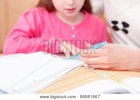 Little girl being taught writing and reading