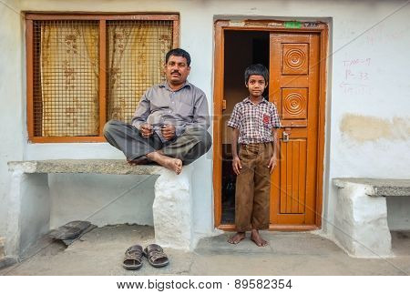 KAMALAPURAM, INDIA - 02 FEBRUARY 2015: Father and son ouside their home in a town close to Hampi