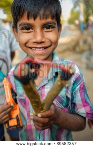 HAMPI, INDIA - 31 JANUARY 2015: Indian boy holding slingshot and toy truck