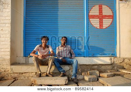 KAMALAPURAM, INDIA - 02 FEBRUARY 2015: Local indian men sitting infront of closed shop in a town close to Hampi