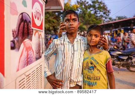 KAMALAPURAM, INDIA - 02 FEBRUARY 2015: Two Indian brothers hugging in street and fooling around with people around them