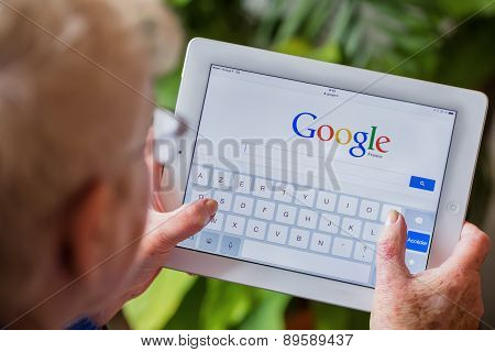 Paris, France - April 27, 2015: Senior Woman Using Tablet With Google Search Home Page On A Ipad Scr