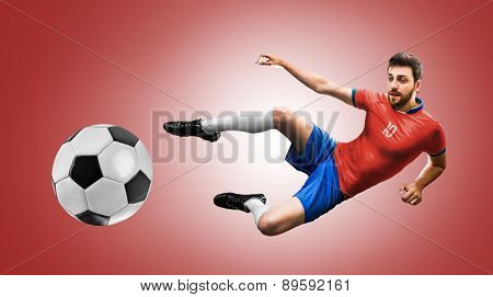 Soccer player on red and blue uniform on red background