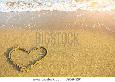 Heart drawn on the sand of ocean beach.