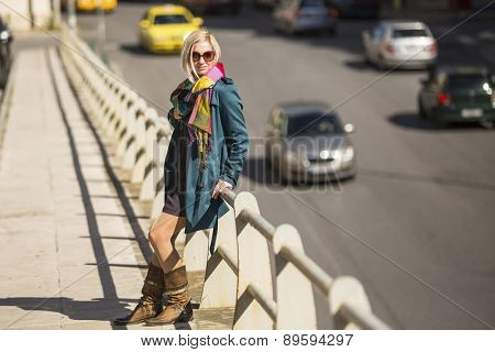Young woman standing near a busy street.