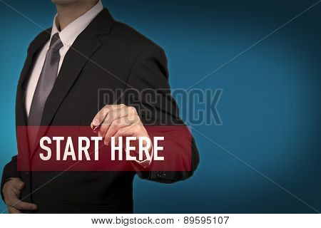 Businessman write Start here word for stat to success in business position.