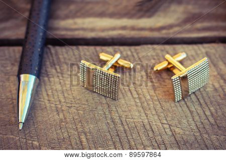 Pen and cufflinks on the old wood background. Toned image.