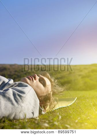 Young Man Lying On The Green Grass.