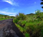 picture of volcanic  - A paved Road cuts through green vegetation under blue partly cloudy skies to the summit and cross of Masaya Volcano National Park  - JPG