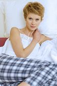 stock photo of pyjama  - Young woman in pyjamas sitting on bed - JPG