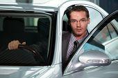 foto of showrooms  - Car salesperson getting in car at showroom - JPG
