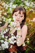 stock photo of heartfelt  - beautiful woman in spring cherry garden with white flowering tree - JPG