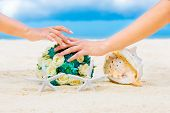 stock photo of beach shell art  - Male and female hands two wedding rings with two starfish wedding bouquet and a large shell on a sandy tropical beach - JPG