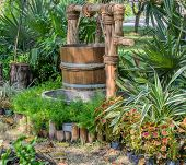 stock photo of groundwater  - Well and wooden bucket in the garden - JPG