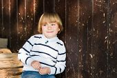 stock photo of pullovers  - Cute little caucasian blond boy leaning on an old wooden wall - JPG