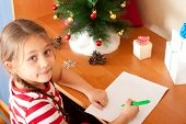 stock photo of letters to santa claus  - charming little girl writes a letter to Santa Claus - JPG