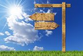 foto of directional  - Wooden directional sign with two empty arrows in opposite direction hanging with a metal chain on a wooden pole on blue sky with clouds sun rays and green grass - JPG