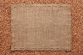 image of buckwheat  - Frame made of burlap with the line lies on buckwheat grains with place for your text - JPG
