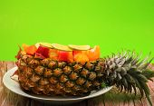 foto of green papaya salad  - Thai style fruit salad inside a pineapple with a green background on a wood table top - JPG