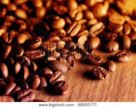 Fresh roasted coffee beans on wooden board. Filtered image: vintage effect.
