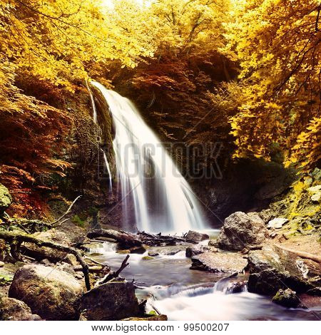 The beautiful waterfall in forest, spring, long exposure. Filtered image: warm cross processed vintage effect.