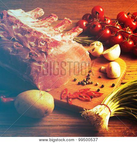 Raw Steak with vegetables on wooden board. Filtered image: vintage effect.