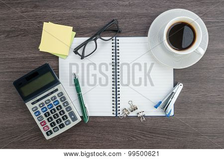 Notebook, Calculator, Stapler And Cup Of Coffee