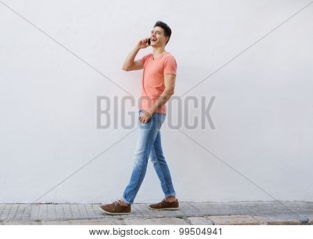 Smiling Man Walking And Listening To Mobile Phone