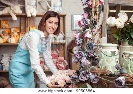Cheerful young saleswoman is working with flowers