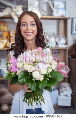 Cheerful young woman is buying bouquet in flower shop