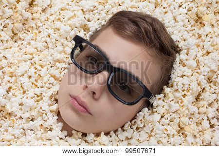 young boy in stereo glasses looking out of popcorn