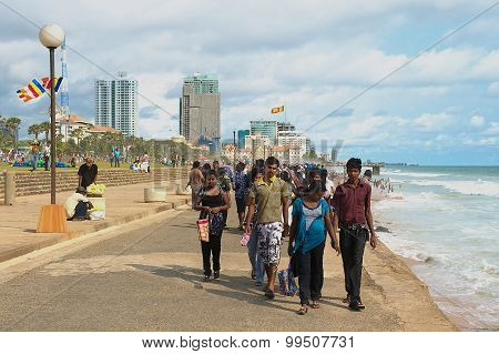 People walk by the seaside in Colombo, Sri Lanka.