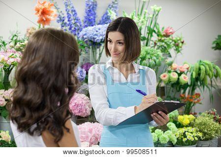 Attractive saleswoman is serving customer in flower shop