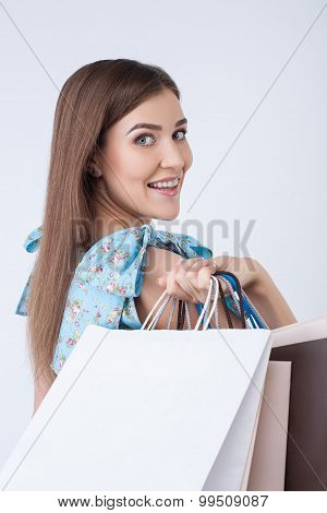 Cheerful young woman is going shopping with pleasure