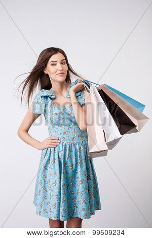 Attractive young woman with packets of bought clothing