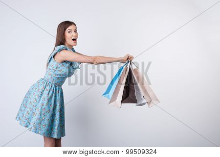 Cheerful young woman is playing with packets