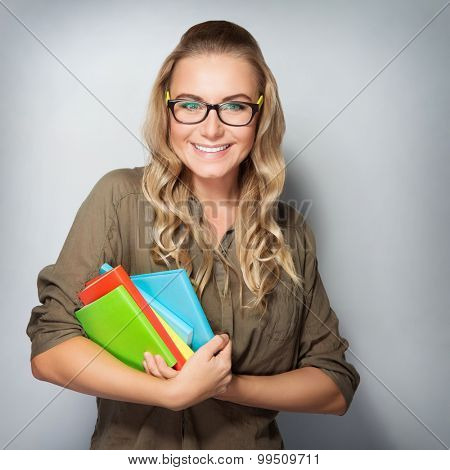 Portrait of happy cute student girl with books in hands over gray background, enjoying first days of education in high school