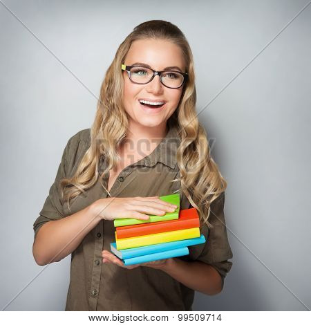 Portrait of cheerful smiling clever student girl with books over gray background, education in the university, enjoying start of educational process