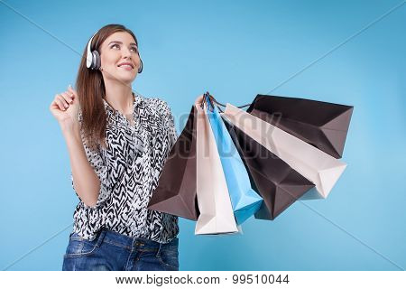 Cheerful young woman with earphones is buying clothing