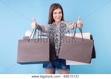 Pretty young woman with packages is gesturing positively