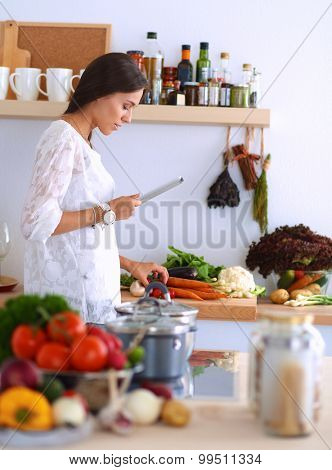 Young woman using a tablet computer to cook in her kitchen