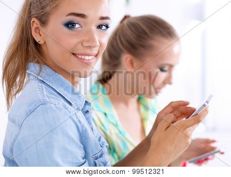 Two girls look on the phone photo together