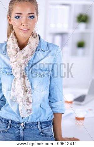 Attractive young  woman standing  near table in office