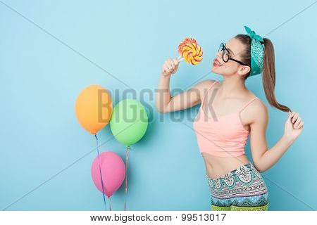 Cheerful young styled woman is eating candies